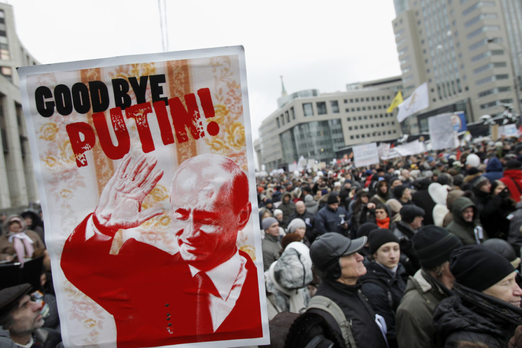"Protesters carry a depiction of Putin bearing the words ""Good Bye Putin"" as they gather to protest against alleged vote rigging in Russia's parliamentary elections on Sakharov avenue in Moscow,  Russia, Saturday, Dec. 24, 2011. Tens of thousands of demonstrators on Saturday cheered opposition leaders and jeered the Kremlin in the largest protest in the Russian capital so far against election fraud, signaling growing outrage over Prime Minister Vladimir Putin's 12-year rule. (AP Photo/Ivan Sekretarev)"